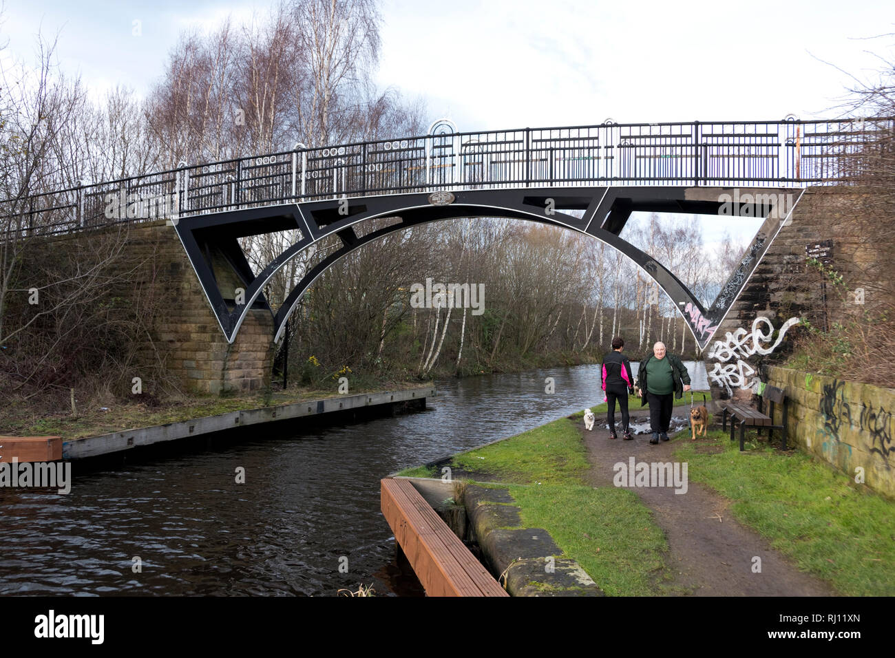 Sheffield, UK – January 24 2016 : two dog walkers greet one another beneath Brown Bayley Bridge no. 10a on the Sheffield and Tinsley Canal - Stock Image
