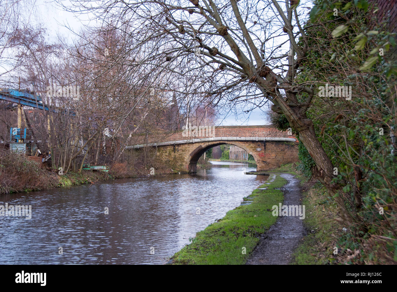 Sheffield, UK – January 24 2016 : A wet towpath leads to Bacon Lane Bridge No 6 on a winter's day on the Sheffield and Tinsley Canal - Stock Image