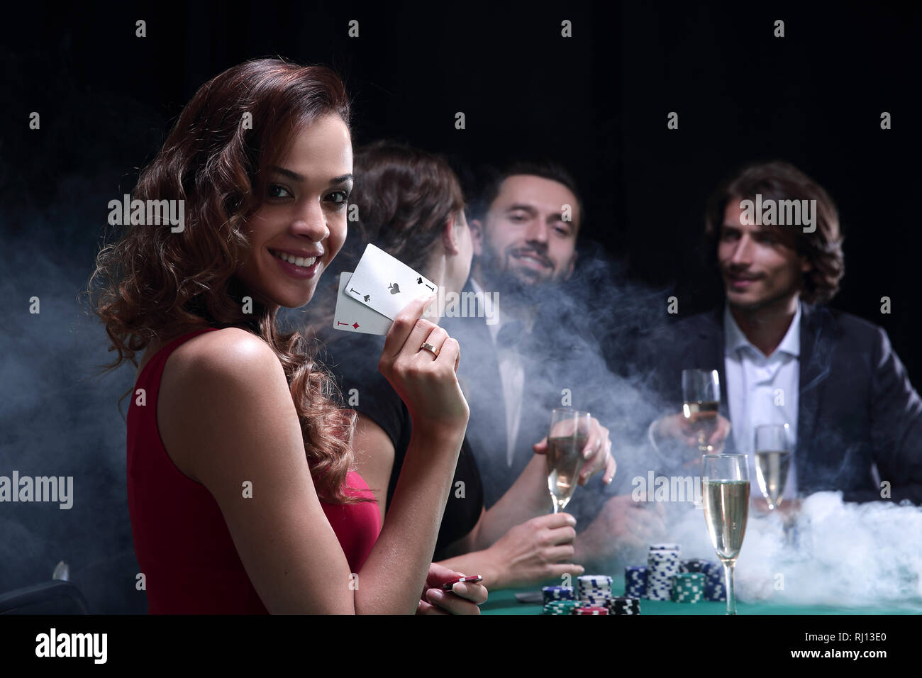 young brunette woman playing poker on black background - Stock Image