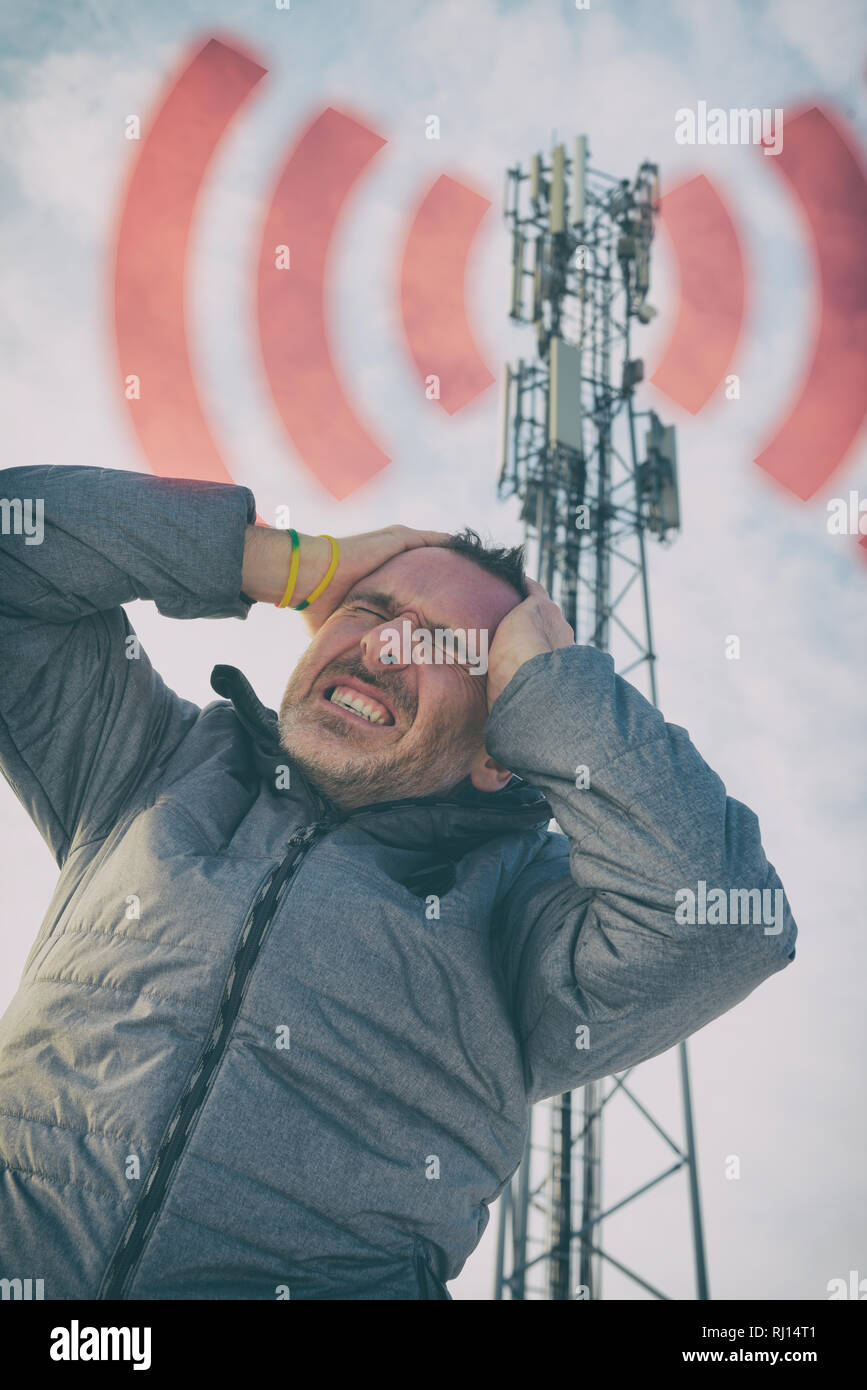 Man holding his head near the BTS. Harmful radiation from cellular network transmitters concept - Stock Image
