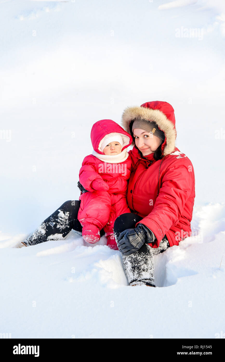Mom and daughter spend time together for a walk on a snowy winter day - Stock Image
