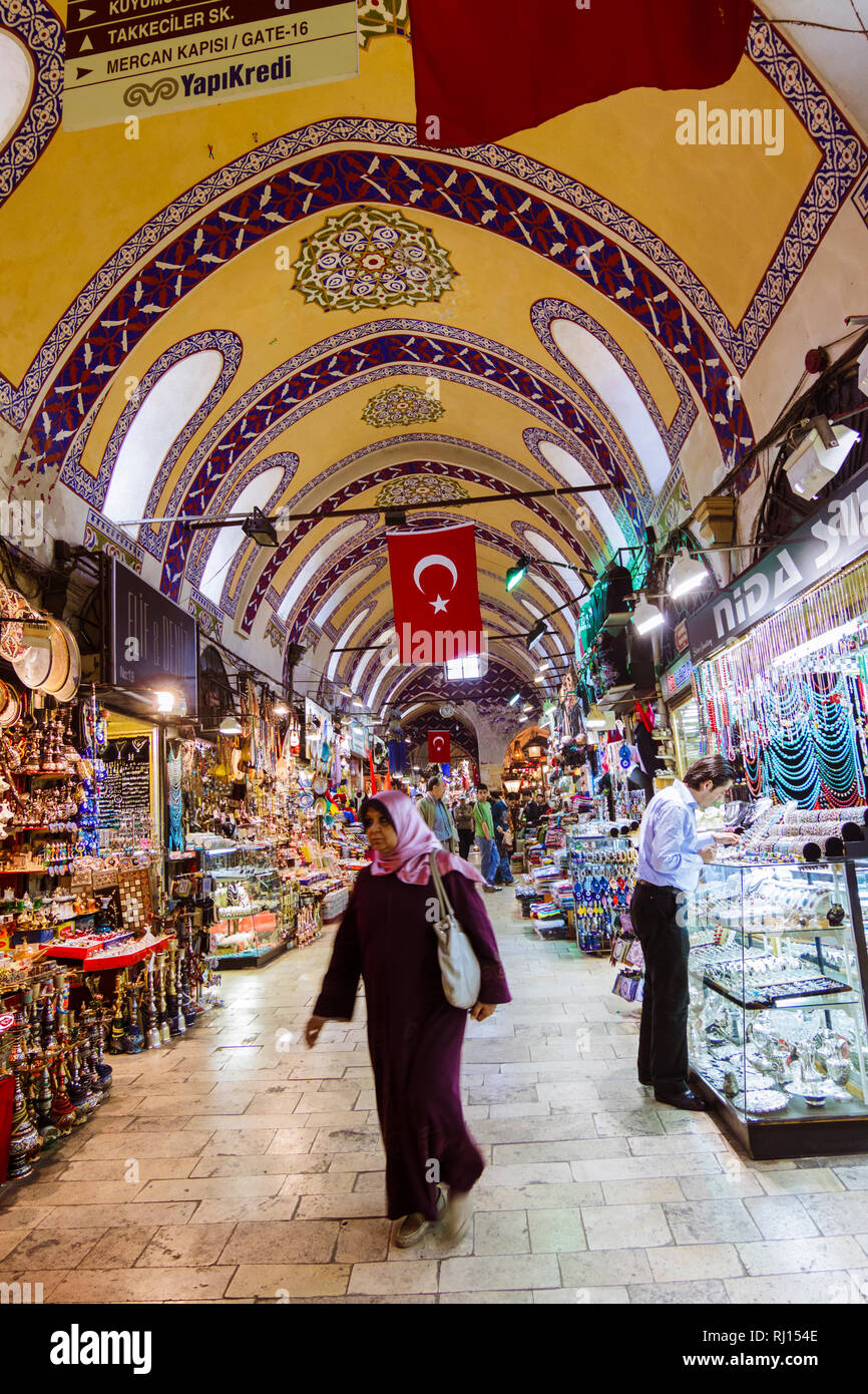 Istanbul, Turkey : A Turkish woman walks past shops inside the Grand Bazaar (Kapalıçarşı) one of the largest and oldest covered markets in the world w - Stock Image