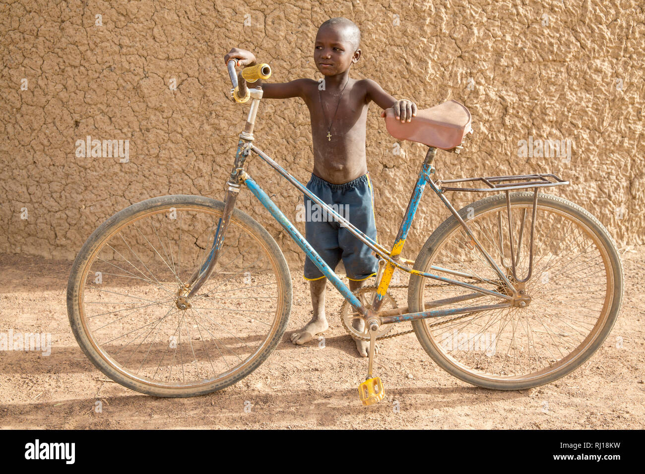 Samba village, Yako Province, Burkina Faso: A young boy with an adult bike. Stock Photo
