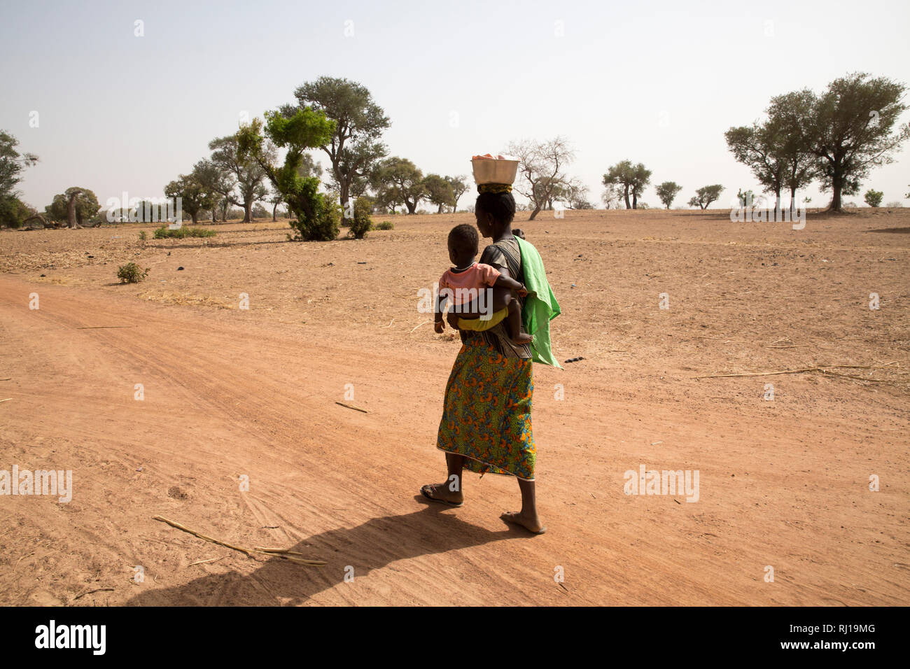Samba village, Yako Province, Burkina Faso; Sally Zoundi, 35, with her baby Salomon Zoundi, 15 months, on her way to work at the local goldmine to support her family. Stock Photo