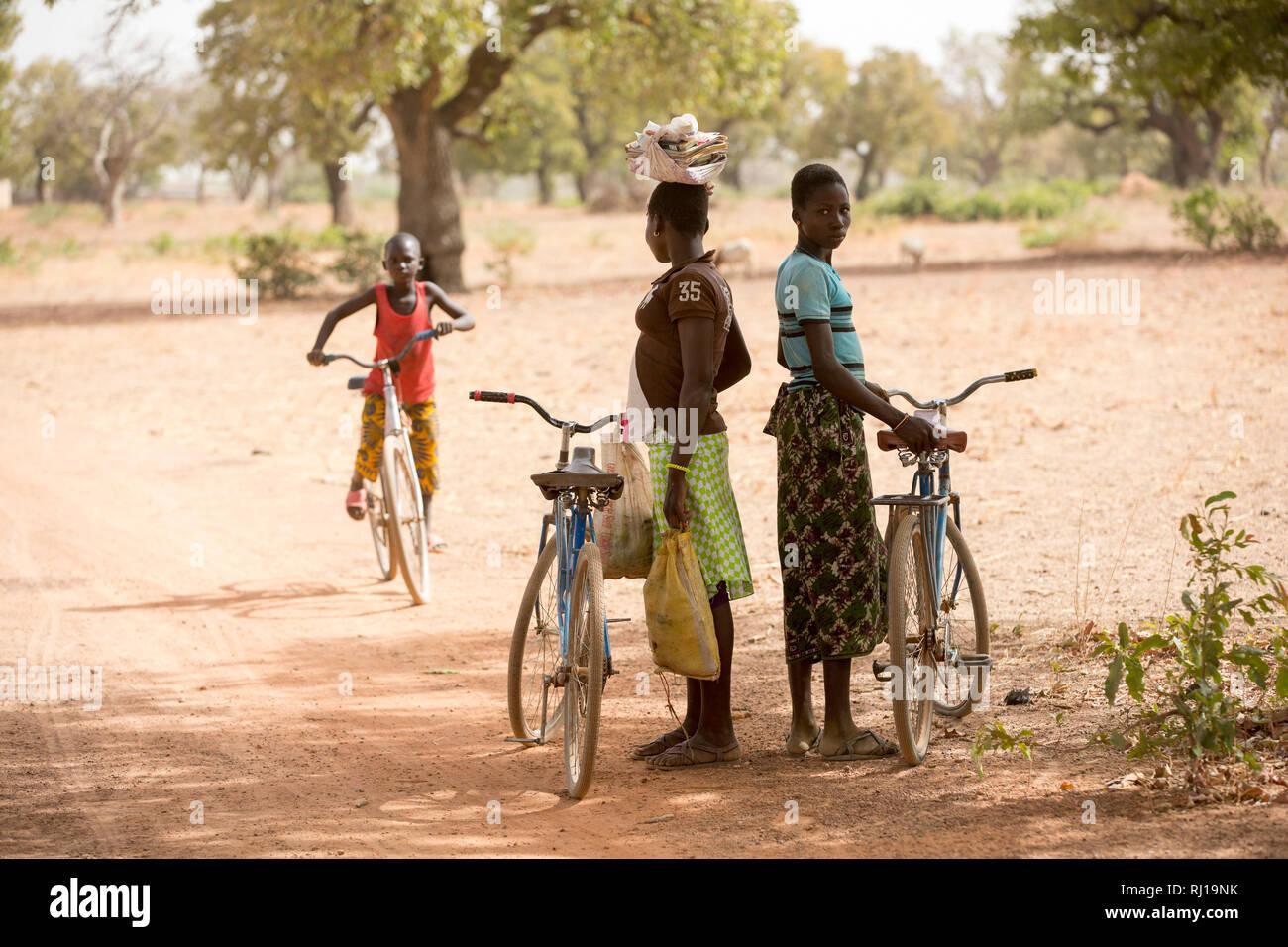 Samba village, Yako Province, Burkina Faso; schoolgirls on their way home from school wait in the shade for a friend. Stock Photo
