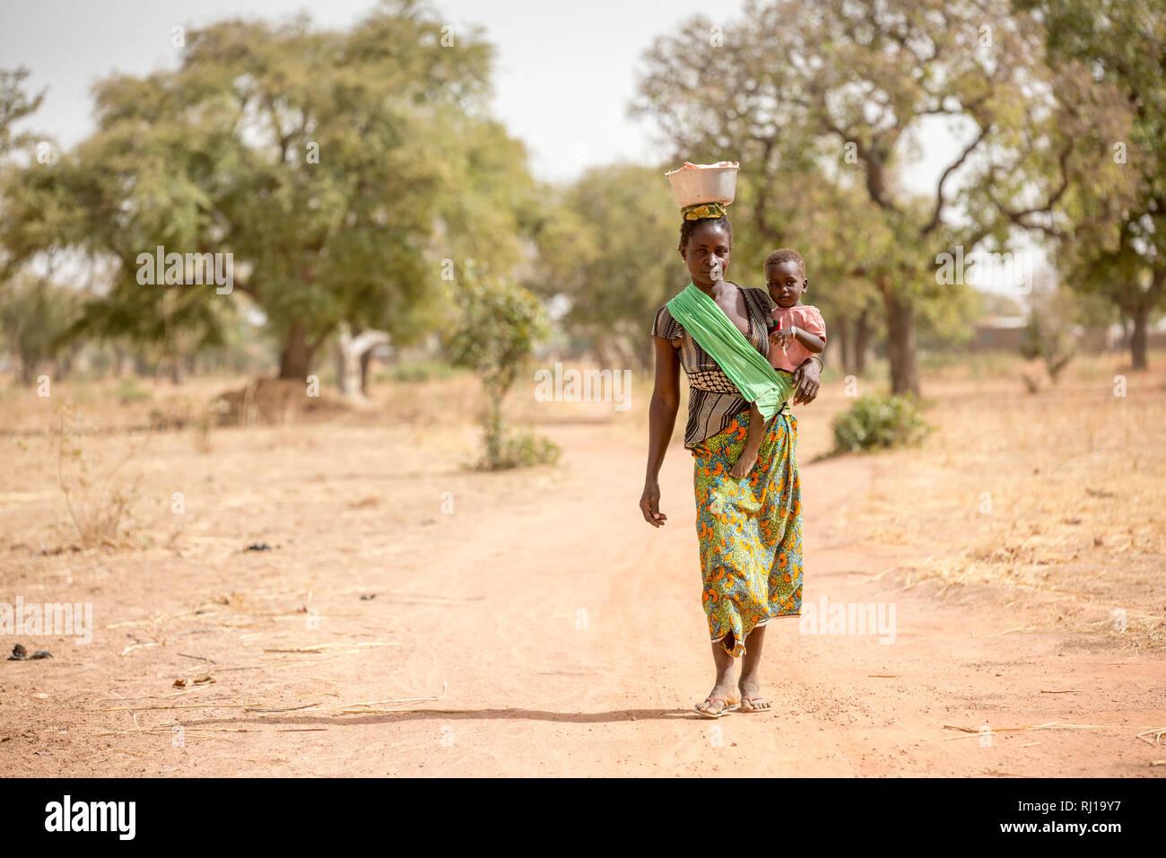 Samba village, Yako Province, Burkina Faso; Sally Zoundi, 35, with her baby Salomon Zoundi, 15 months, on her way to work at the local goldmine to support her family. Stock Photo
