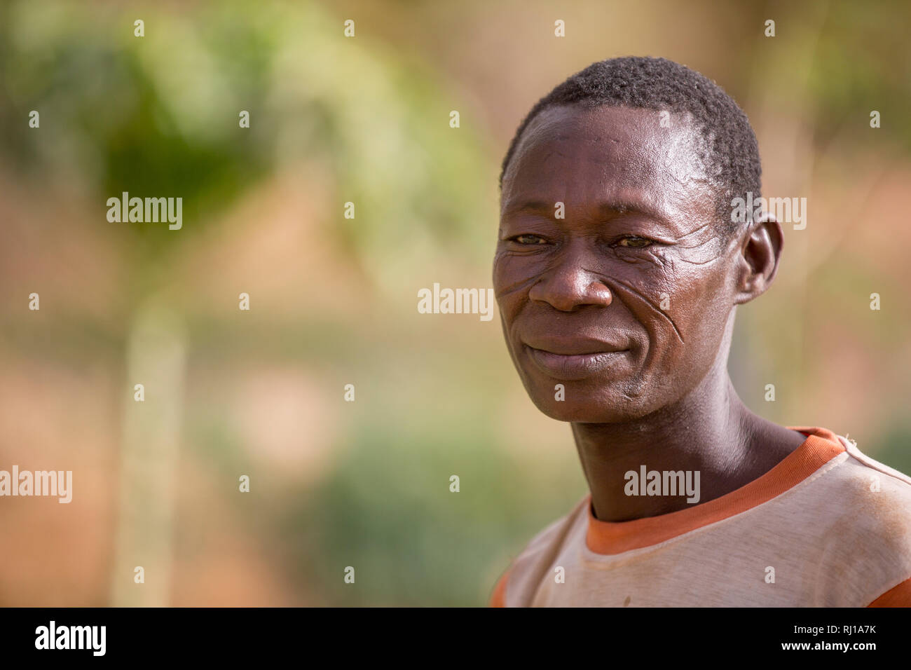 Samba village, Yako Province, Burkina Faso: Portait of Denis Zoundi, 45,with tribal scars, while watering crops on his market garden. - Stock Image