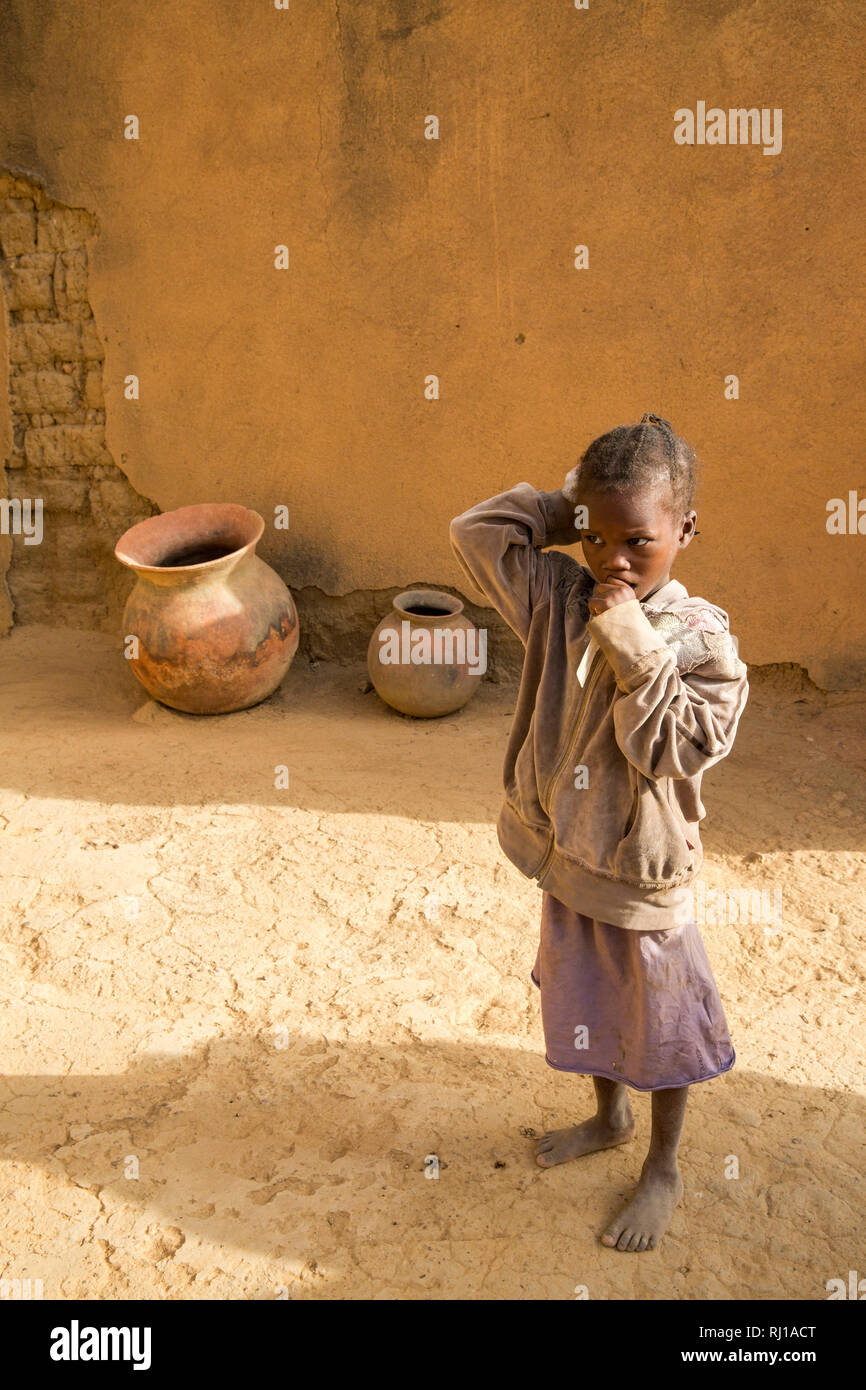 Samba village, Yako Province, Burkina Faso : a young girl, watches while her mother talking to other villagers. Stock Photo
