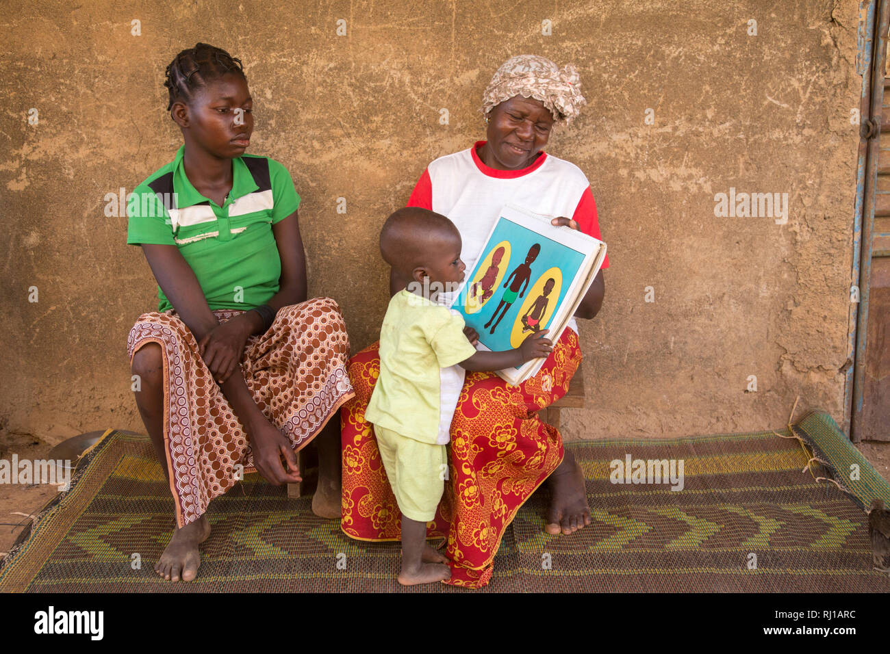 Samba village, Yako Province, Burkina Faso: Abzetta Sondo, 19, and her child suffering from acute malnutrition, get instruction from Helene Pagoundba, nutrition education committee member. Stock Photo
