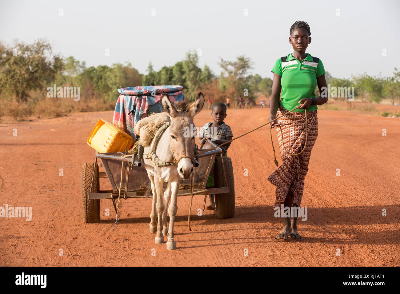 Samba village, Yako Province, Burkina Faso: Abzetta Sondo, 19, returns with full water  container from the well for her household. Stock Photo
