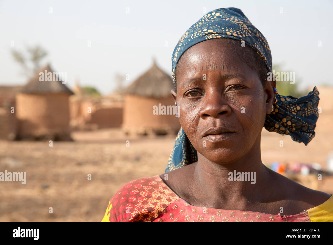 Kourono village, Yako province, Burkina Faso; A portrait of a woman with tribal marking on her face, in front of village grain stores. Stock Photo