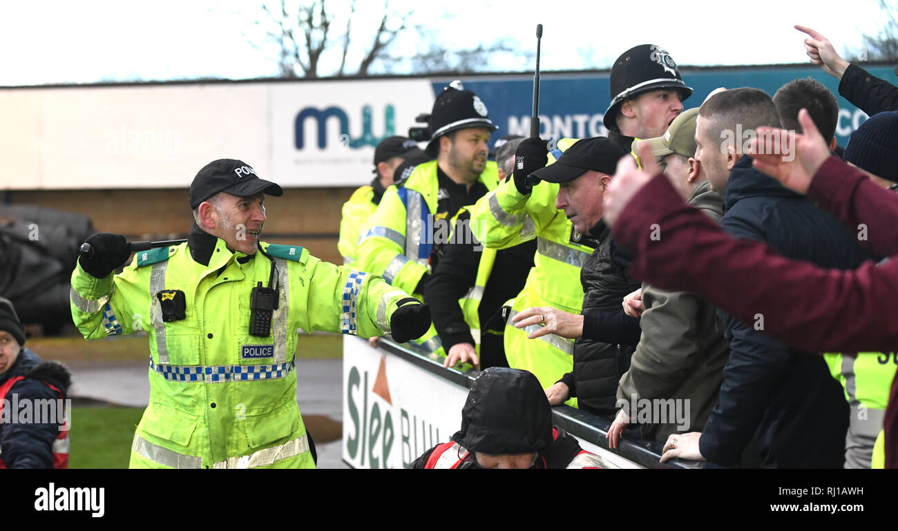 British police officer with batons drawn policing football match during crowd disturbance UK - Stock Image