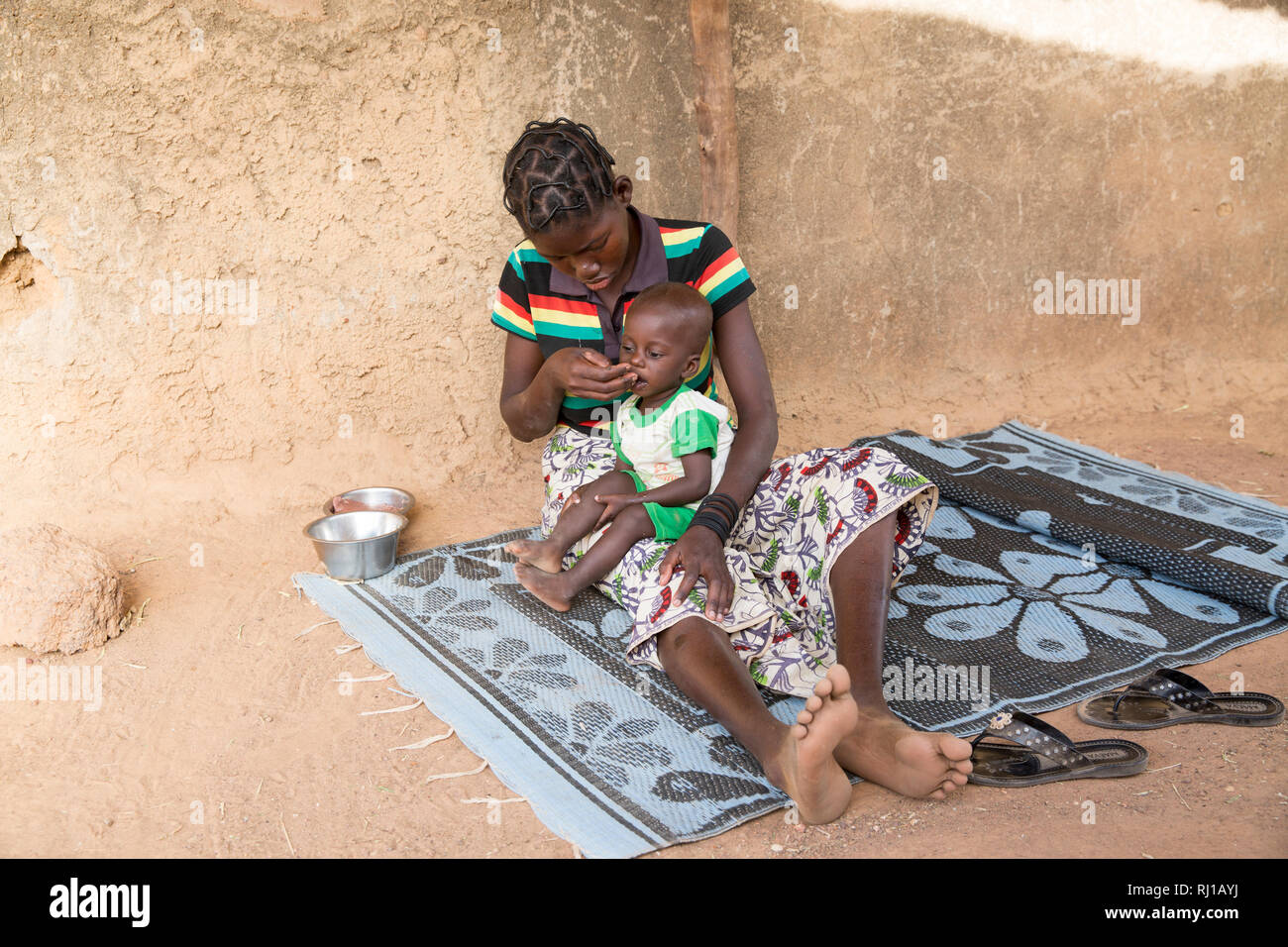 Samba village, Yako Province, Burkina Faso: Abzetta Sondo, 19, and her child Noel Nougtara, 15 months. Her baby is suffering from acute malnutrition. Stock Photo