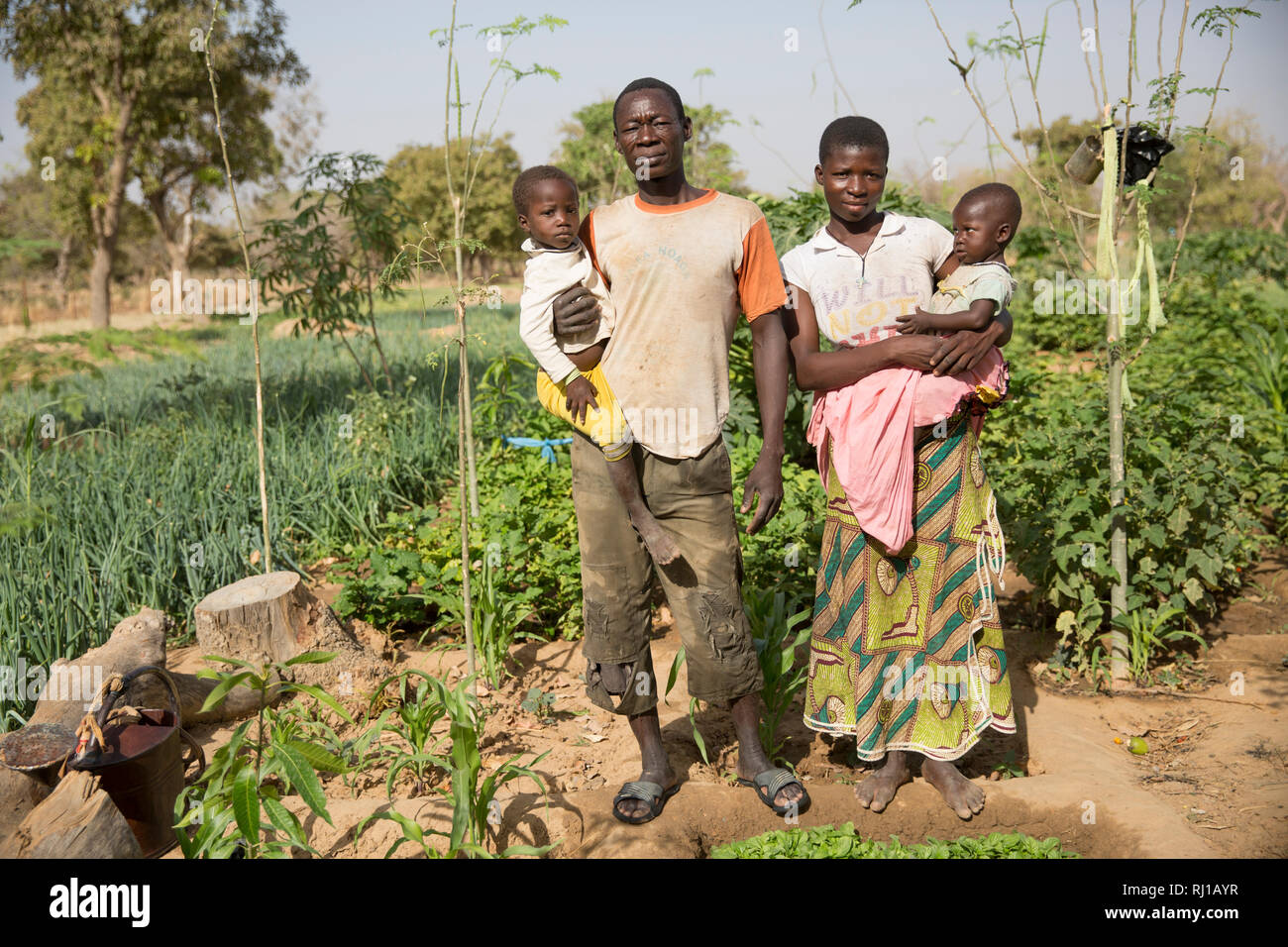 Samba village, Yako Province, Burkina Faso: Denis Zoundi, 45, with his wife Collette Guiguemde, 26, their  baby Ornela Divine Zoundi, 18 months, and  four-year-old daughter Eulalie Zondi at his market garden. - Stock Image