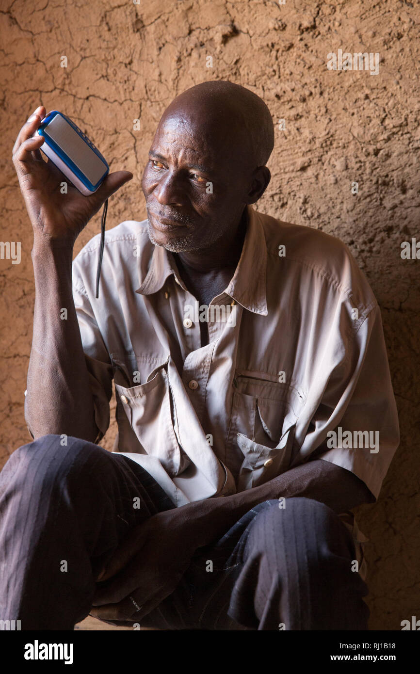 Samba village, Yako Province, Burkina Faso: A house-holder listens to an educational radio programme on nutrition broadcast by the local Natigmbzanga Radio. Stock Photo