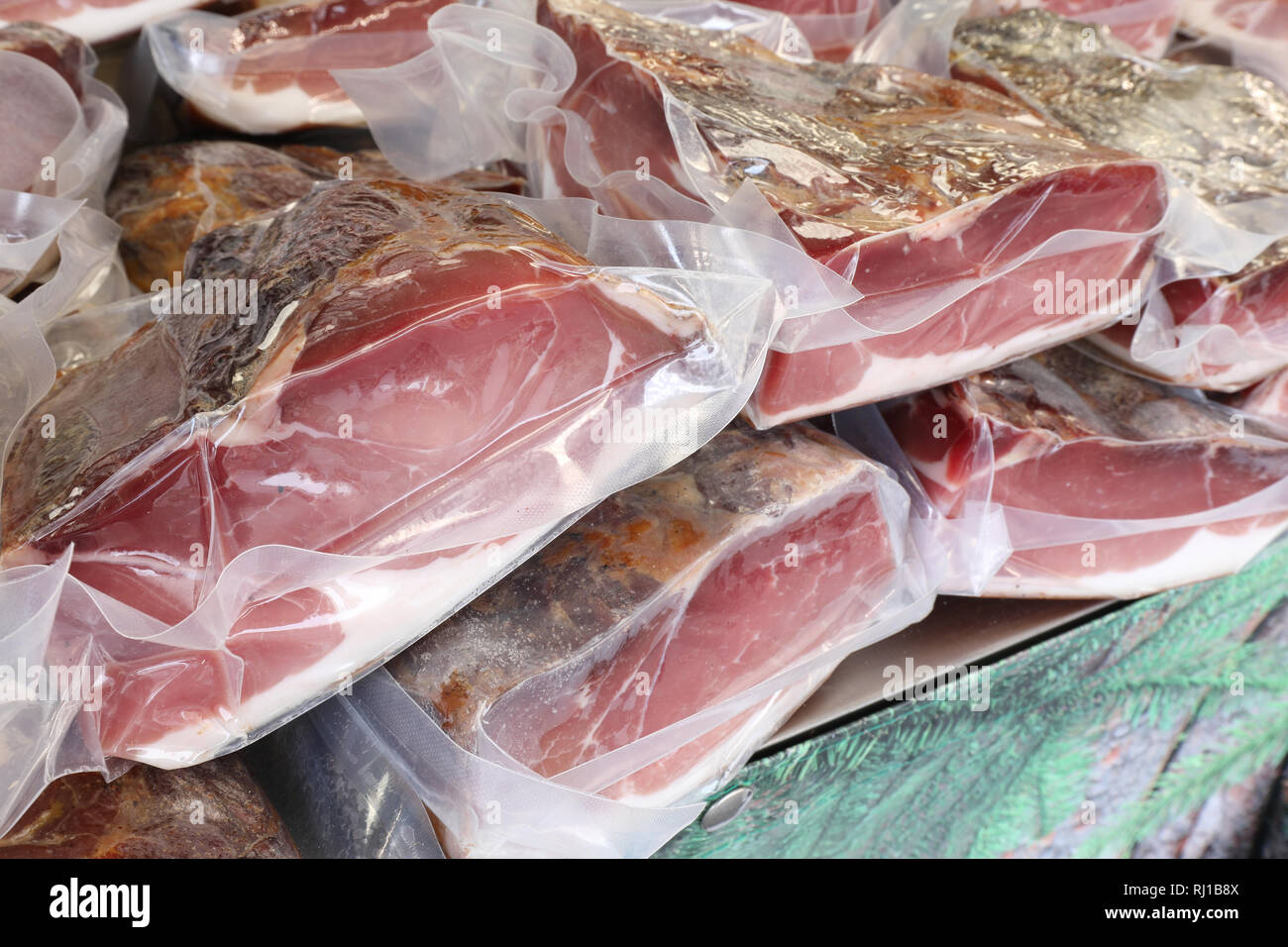 vacuum-packed smoked meats for retail sale in the local market - Stock Image