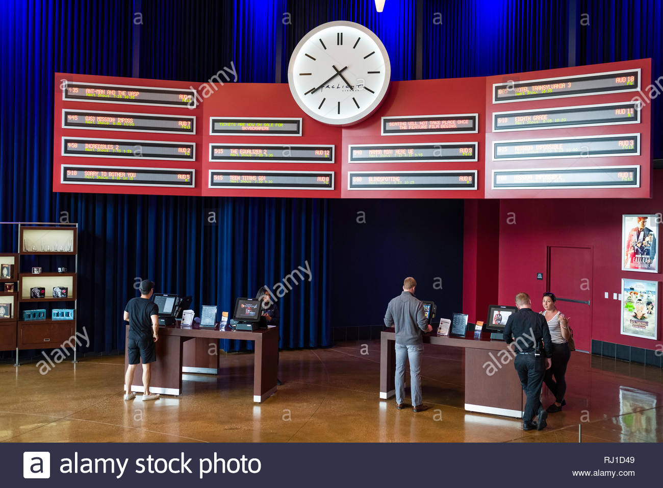 Large analog clock and digital displays of movie times above self-service ticket kiosk in the lobby of the Arclight Cinemas, Santa Monica Place, Santa - Stock Image
