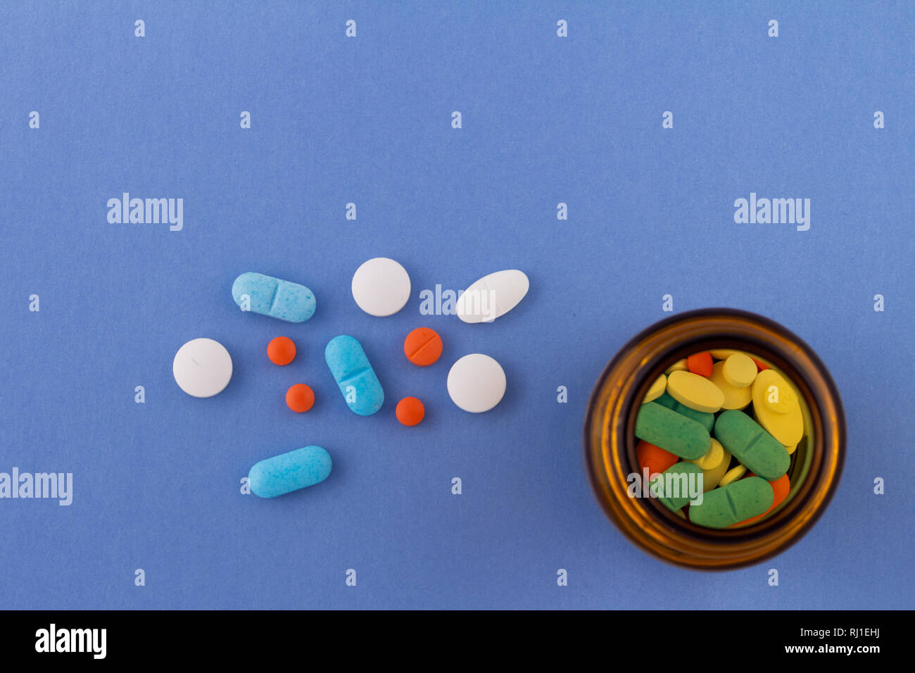 Colored pills on a light blue background next to a glass bottle containing drugs. Drugs for use in humans. Stock Photo