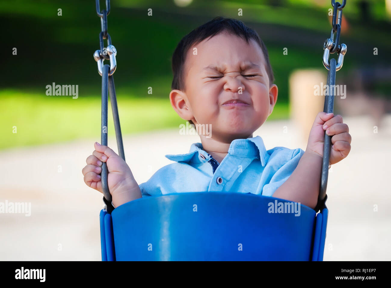 Little boy riding a playground swing with an expression of fear, holding on with a tight grip because he is scared. - Stock Image