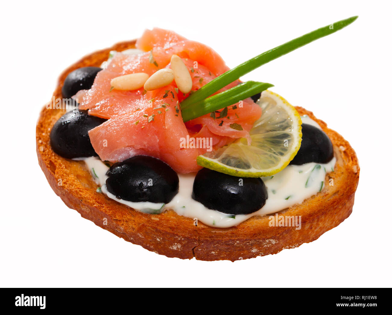 Sandwiche with salmon and olives on white sauce. Isolated over white background - Stock Image