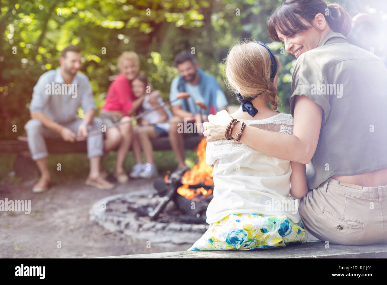 Rear view of mother sitting with arm around daughter while camping at park - Stock Image