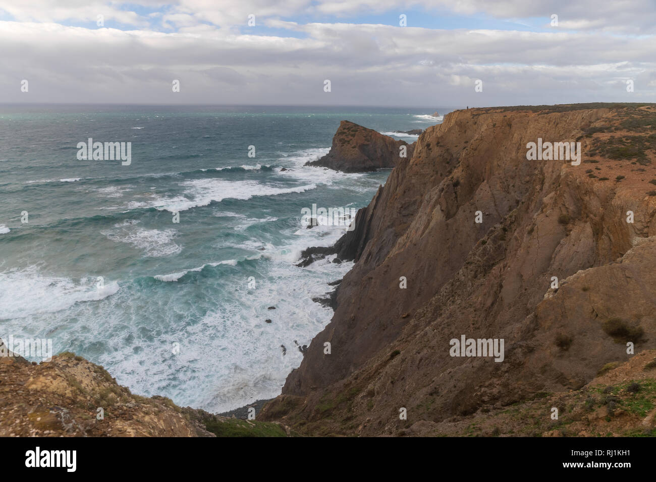 Famous place in south Portugal, Aljezur city, Arrifana beach, The rocky coast, waves of Atlantic Ocean, sharp rocks, azure water, yellow flowers, arch - Stock Image
