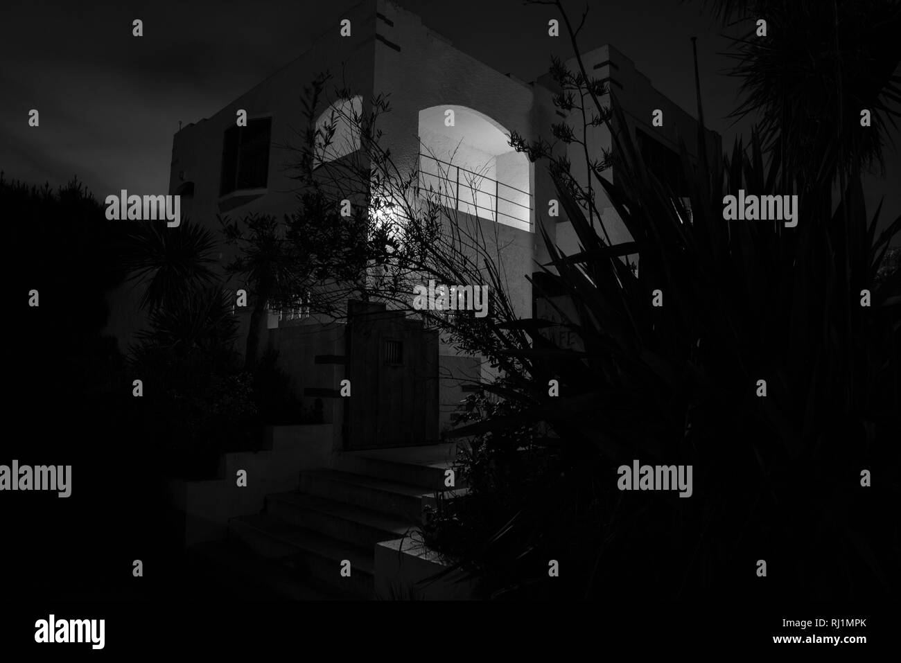 Black and white image deco style house spooky in darkness of night from street Stock Photo