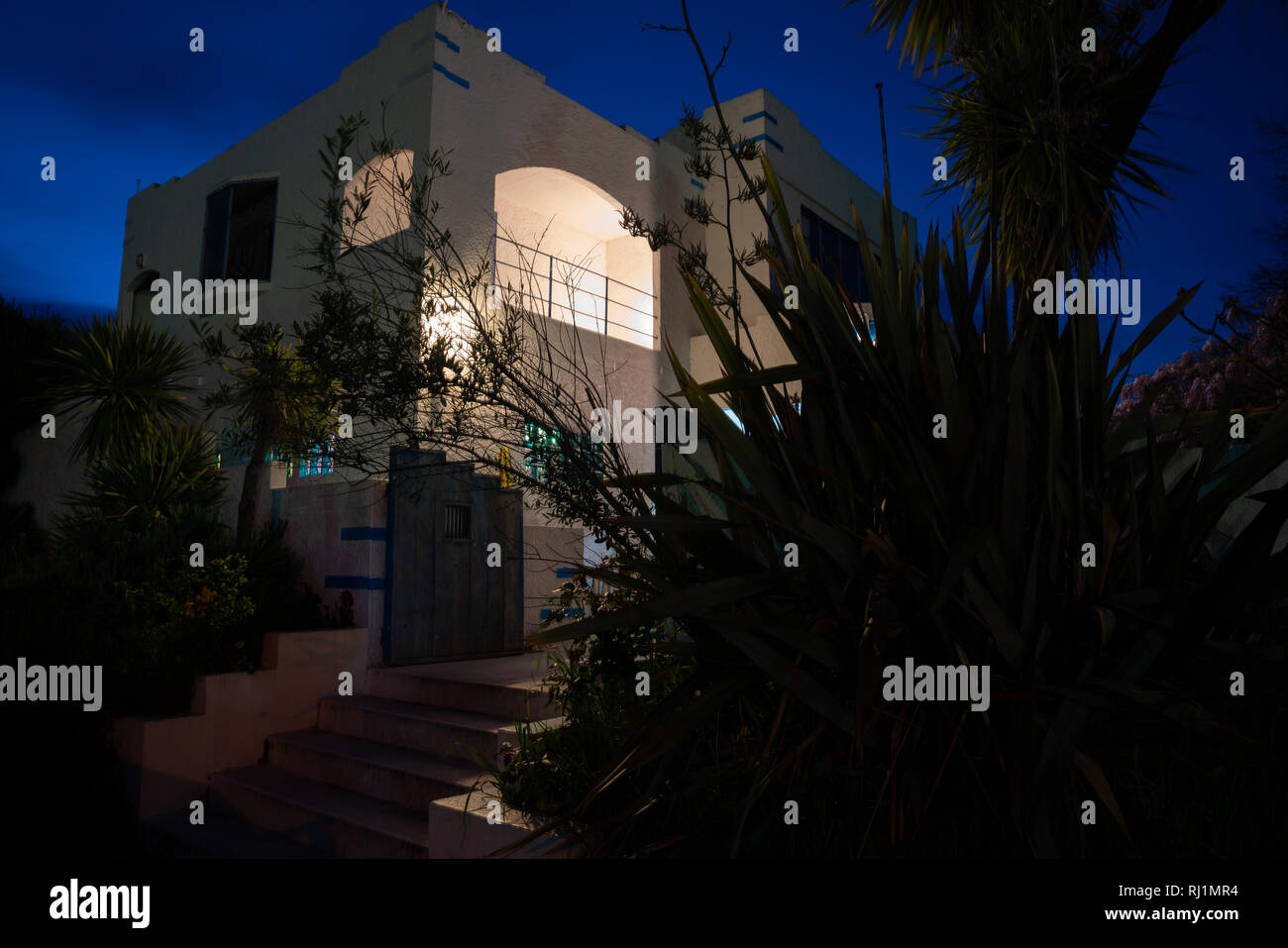 Deco style house spooky in darkness of night from street - Stock Image