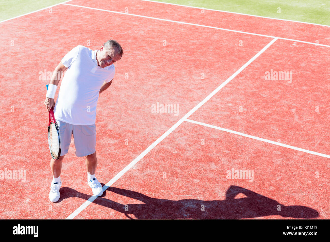 Full length of senior man standing with backache on red court during match on sunny day - Stock Image