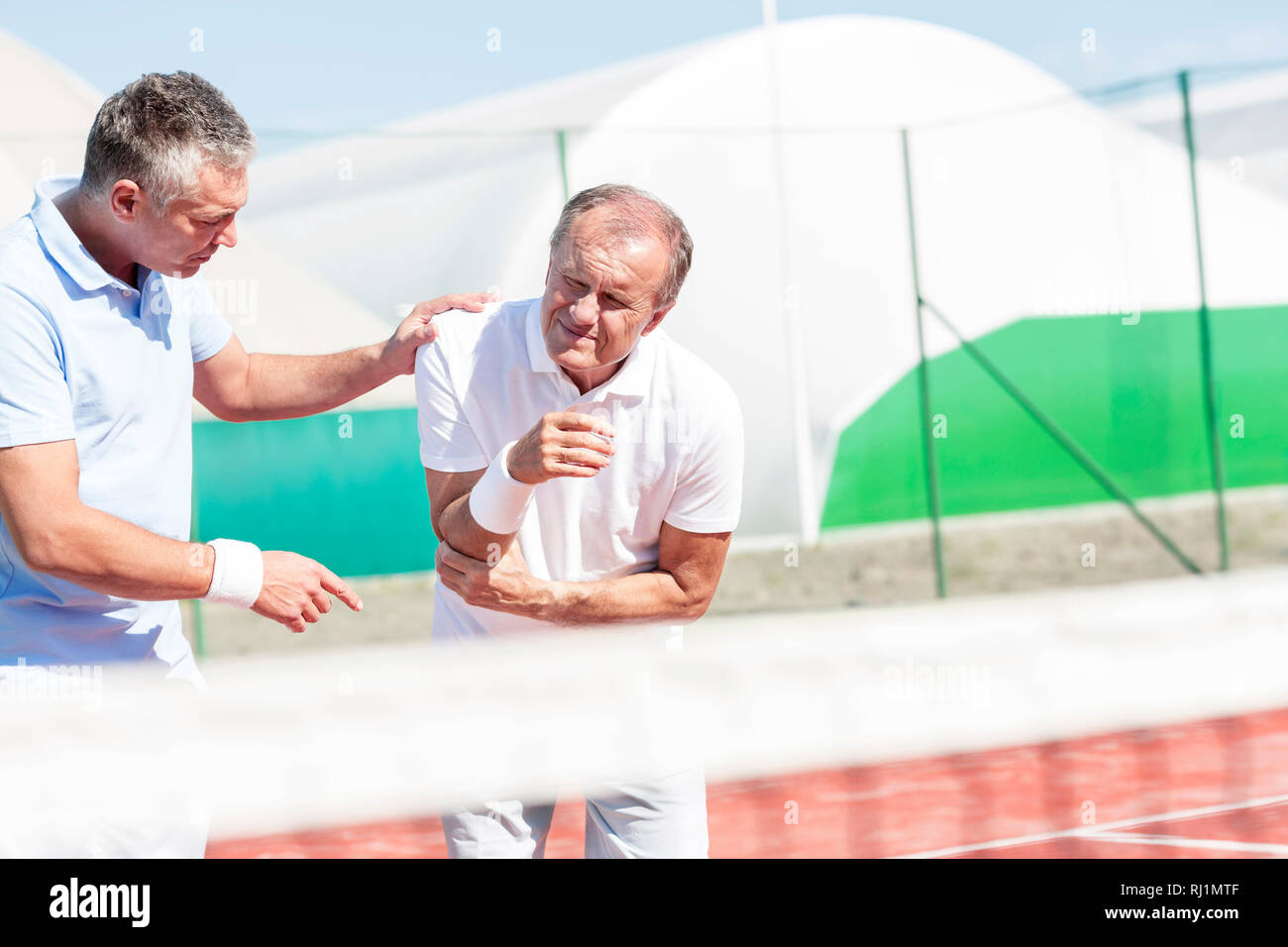 Mature man helping senior friend with elbow injury while playing tennis on sunny day - Stock Image