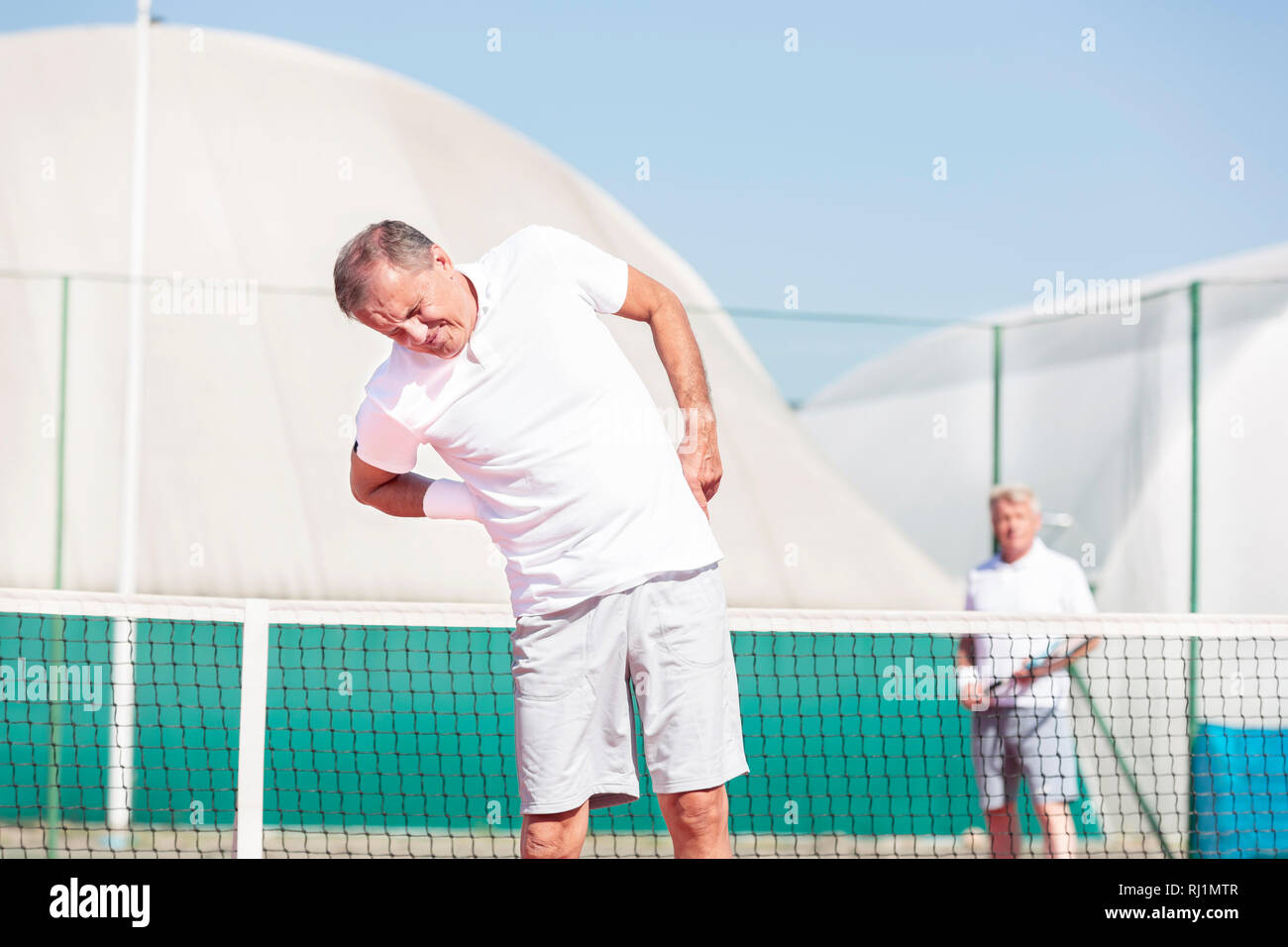 Senior man with backache while standing against friend during tennis match on sunny day - Stock Image