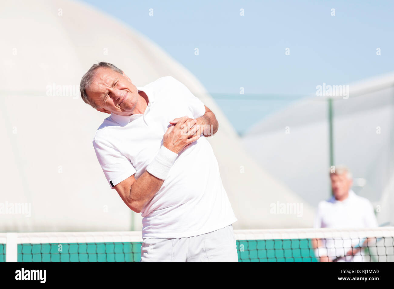 Senior man grimacing with chest pain while standing against friend during tennis match on sunny day - Stock Image