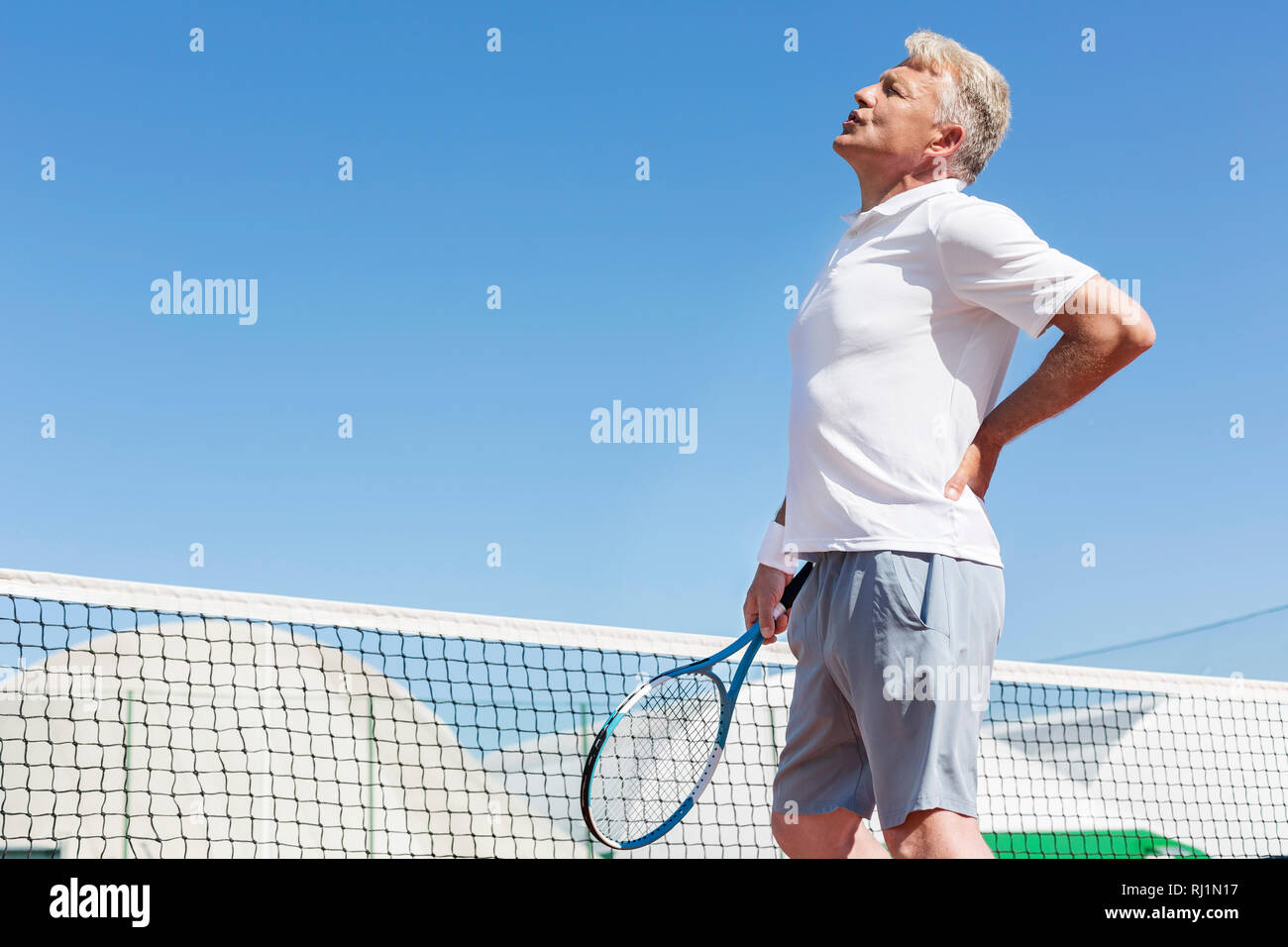 Mature man grimacing with backache while holding tennis racket against clear blue sky on sunny day - Stock Image