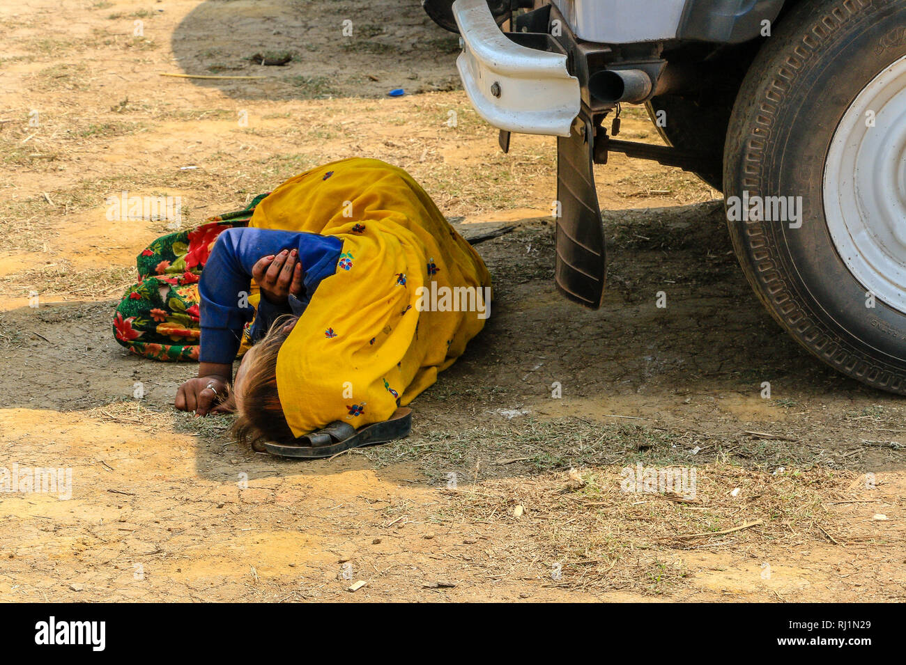 Homeless,Hrijan, untouchable,  Indian woman risks danger by sleeping under the wheels of a truck to escape the heat of the sun, Anjuna  Market, India - Stock Image