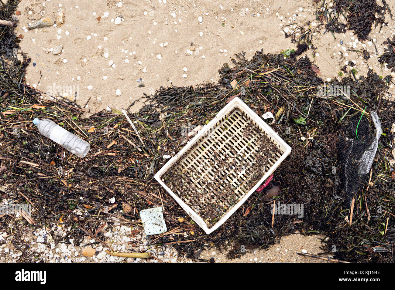 Garbage on the beach. Sea plastic pollution concept. Top view - Stock Image