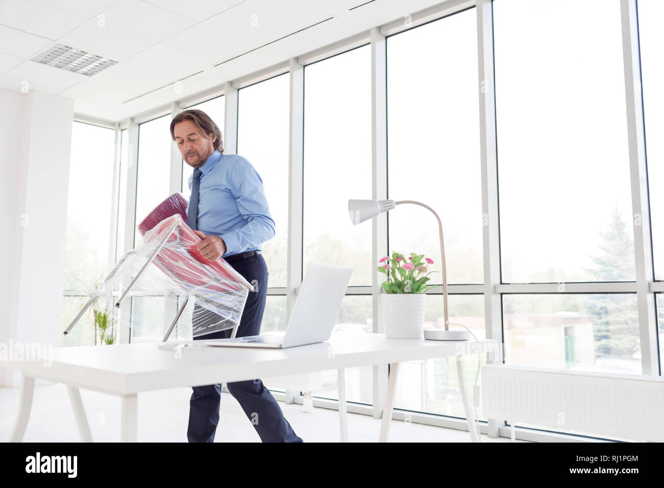 88804e955 Mature businessman carrying chair wrapped in plastic at new office - Stock  Image