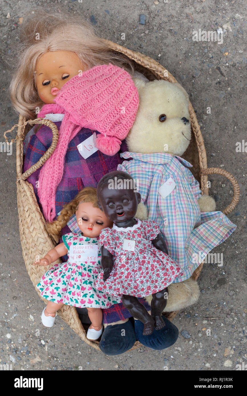 A basket of secondhand dolls at a sale in La Riviere St. Sauveur, near Honfleur, Normandy, France. - Stock Image
