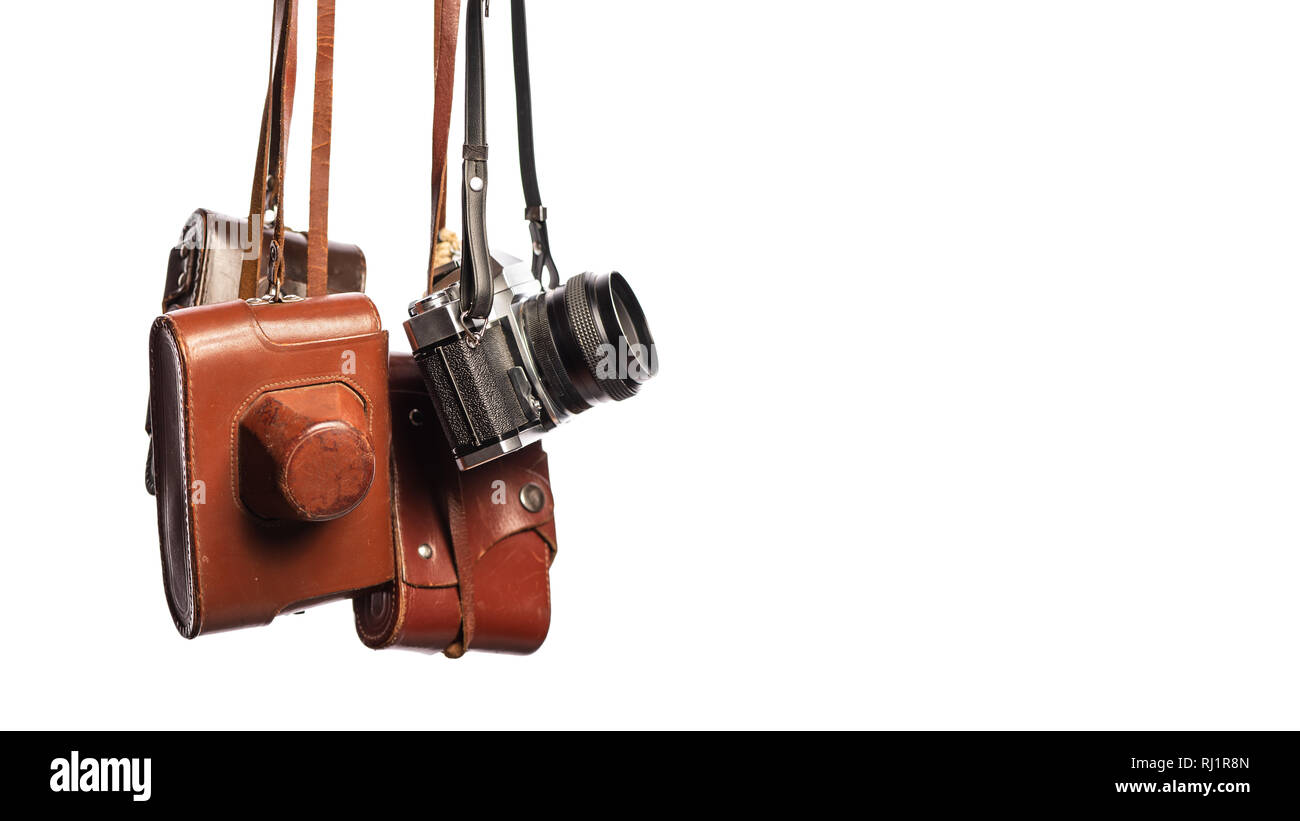 Vintage cameras isolated on white background with clipping path. Old-fashioned analog 35mm cameras in brown leather covers, retro-style. Collectibles  - Stock Image
