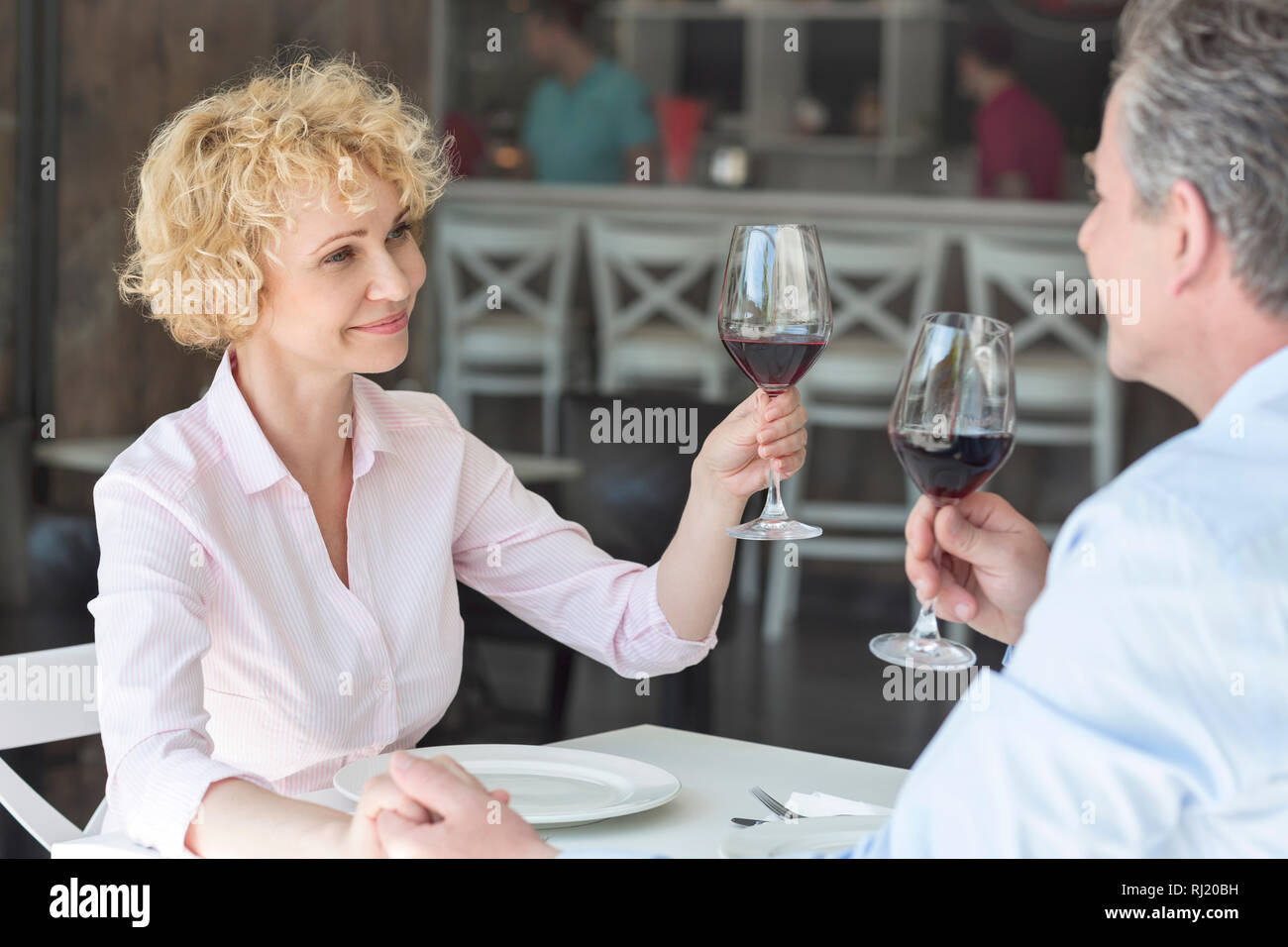 Smiling mature couple toasting wineglasses while sitting at table in restaurant Stock Photo