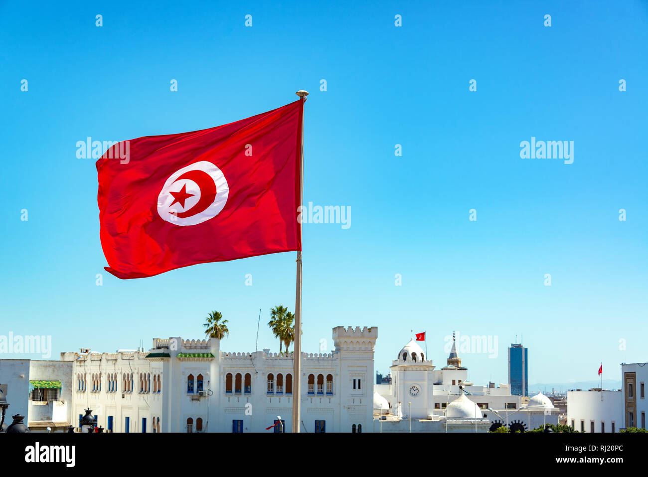 Tunisia flag waving in Tunis with government buildings in the background Stock Photo