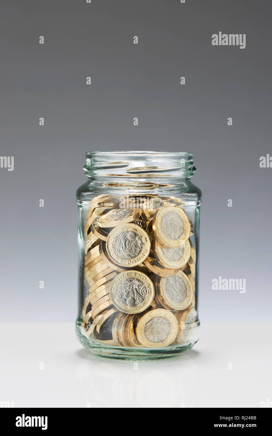 Glass Savings Jar with One Pound Coins Stock Photo