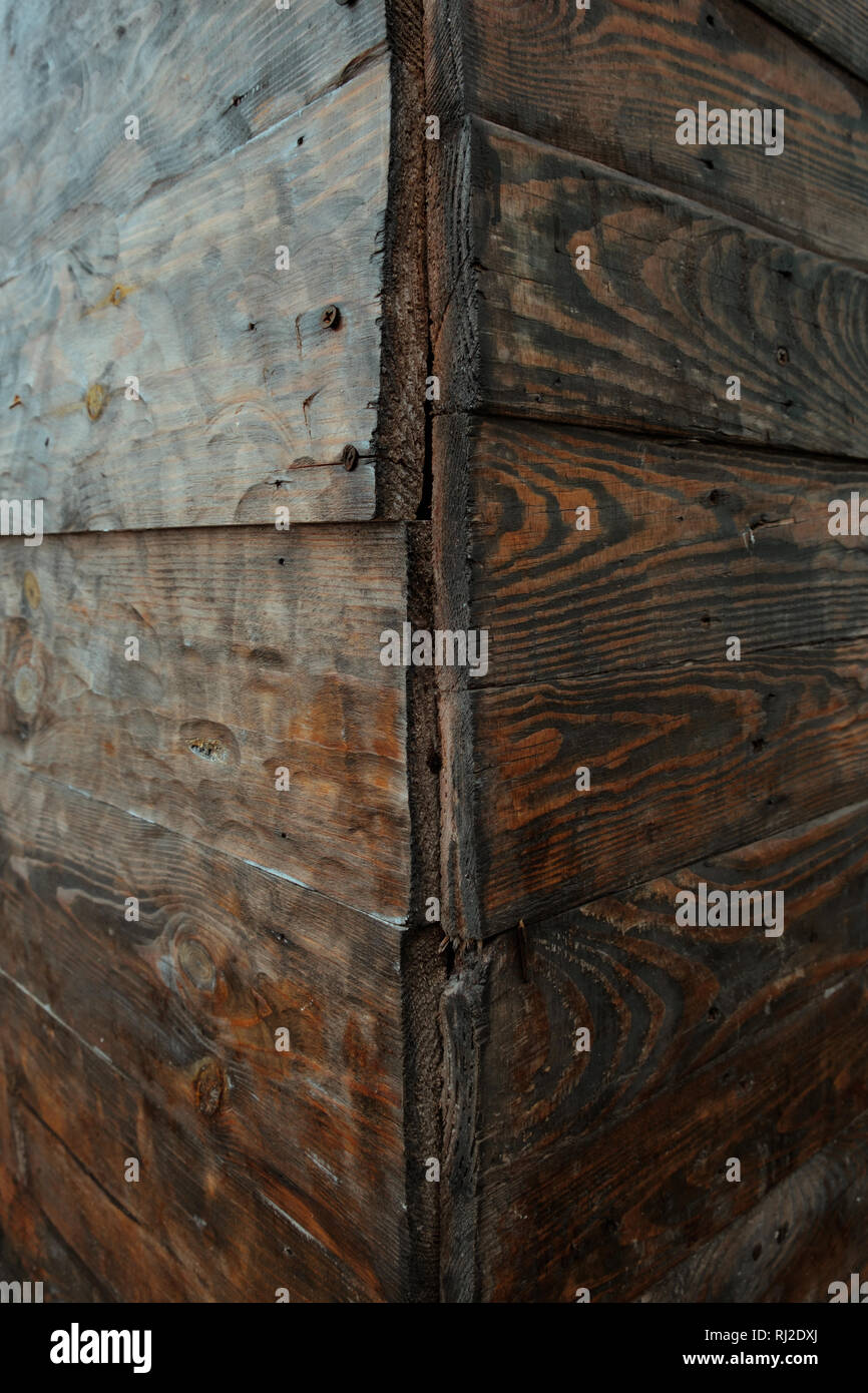 Corner close-up view of a rotten wall made from wood, wooden texture background Stock Photo