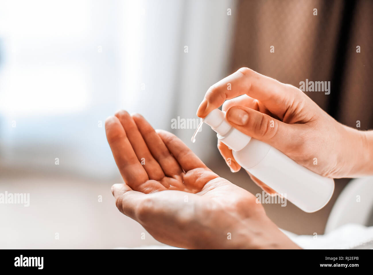 A woman puts on the hands of cosmetics from a bottle or liquid natural soap. Body care concept Stock Photo