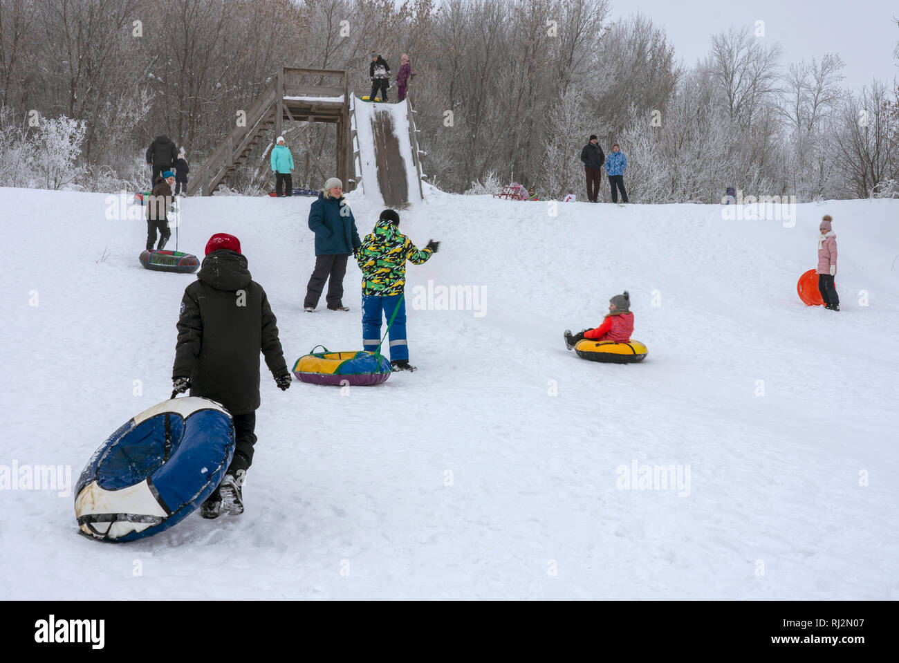 Children in colorful garments slide down the slide on inflatable rings - Stock Image