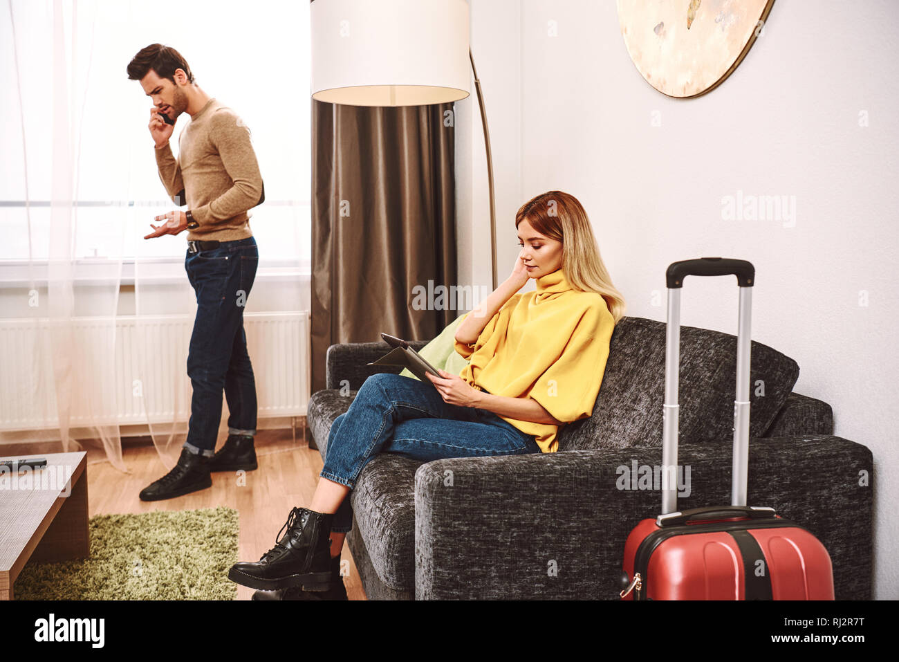 Online hotel research. Young man argue with hotel receptionist by smartphone. Young woman is searching for a new hotels at digital tablet - Stock Image