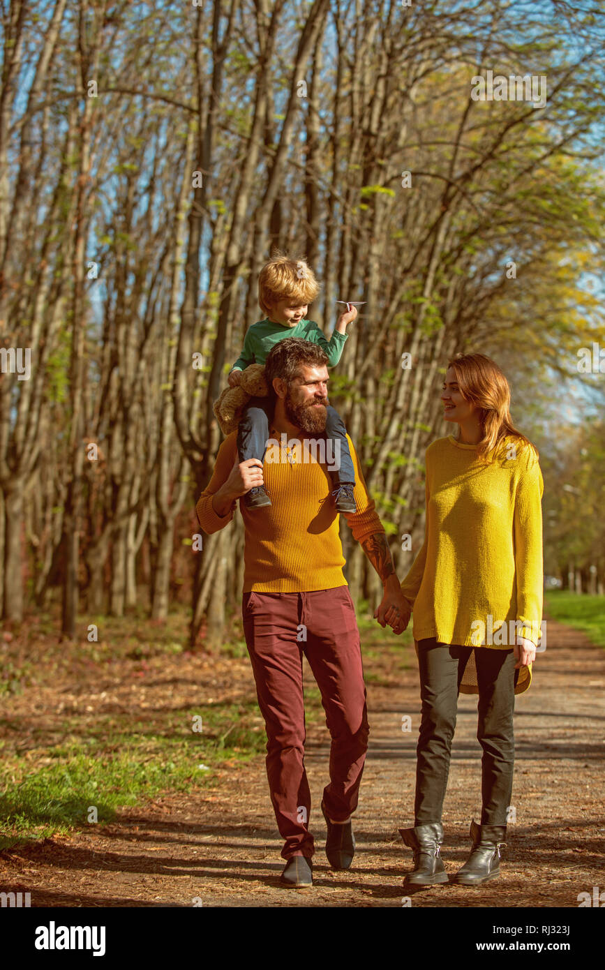 Happy family and little child with paper plane enjoy free time outdoor, freedom concept. Freedom of movement. We are free - Stock Image
