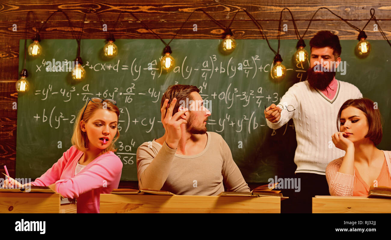 Bearded teacher, lecturer, professor watching students during test, exam, lesson. Cheat on test concept. Students, group mates speaking, asking for - Stock Image