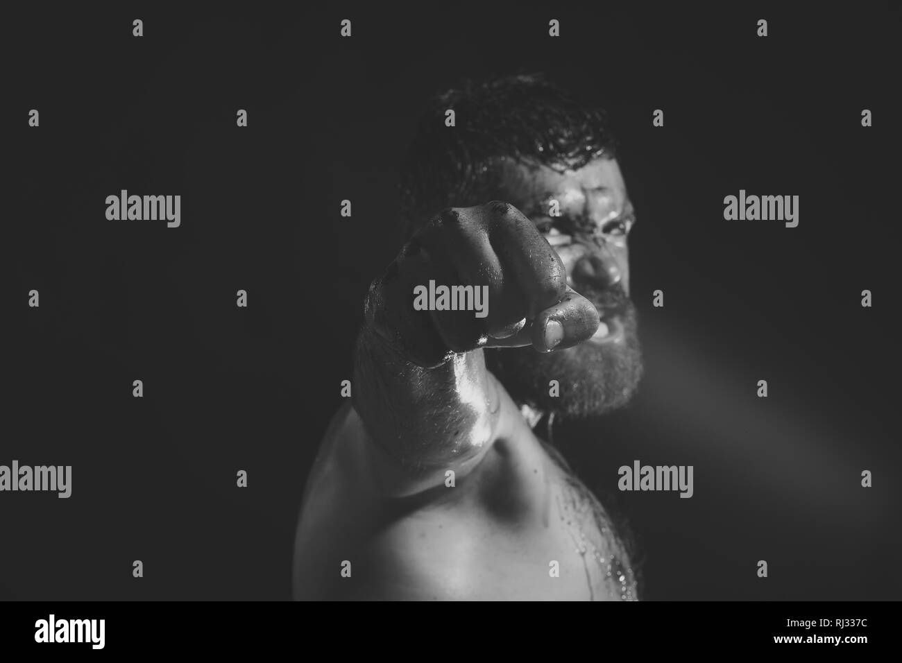 Fist with blood of bearded man on black background - Stock Image