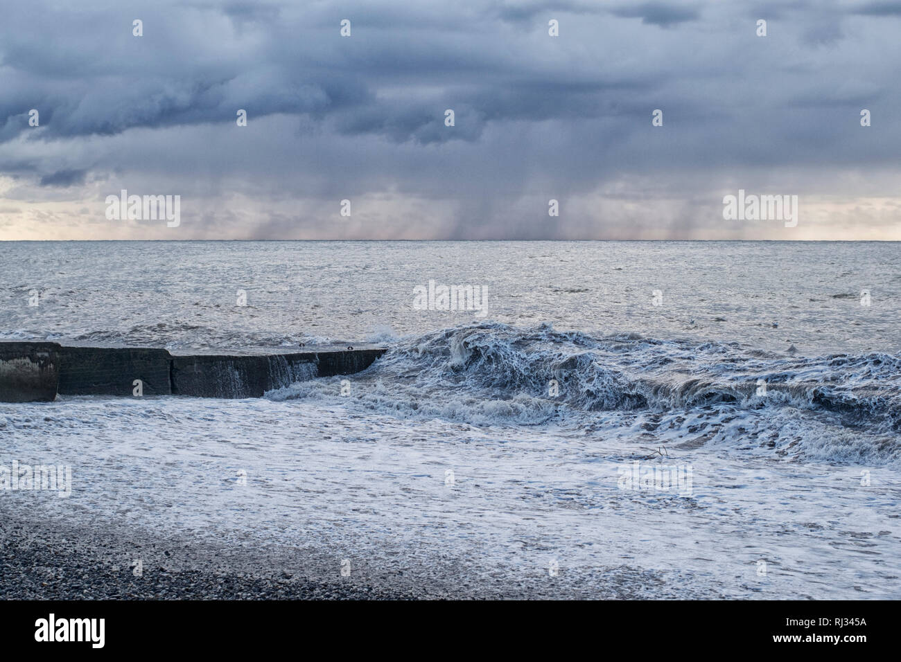 Seascape with a concrete pier during a storm in the rain Stock Photo