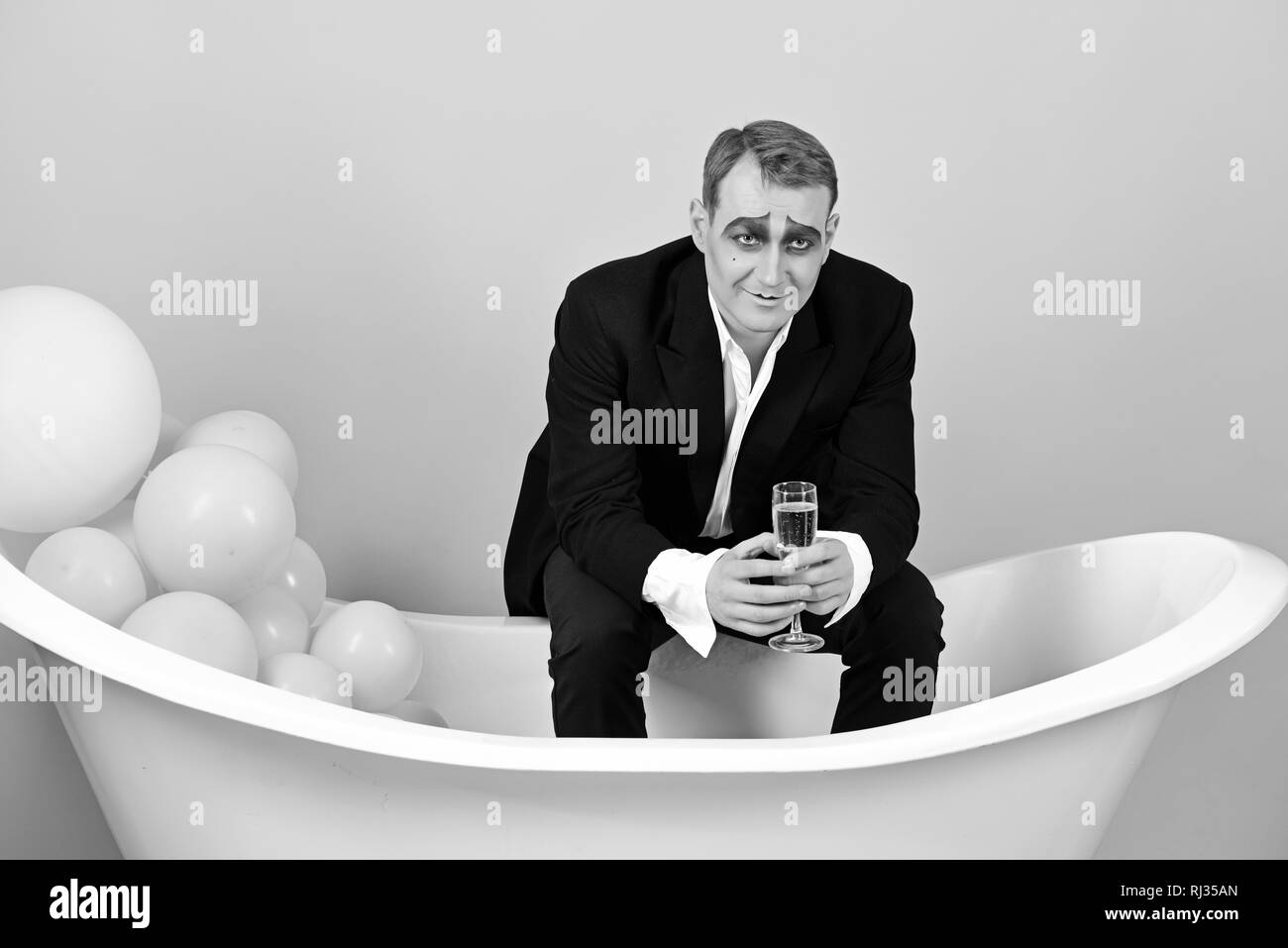 Drinking sparkling wine for festive occasions. Mime actor has celebration party. Mime man celebrate party in bath. Comedian actor enjoy theatre party - Stock Image